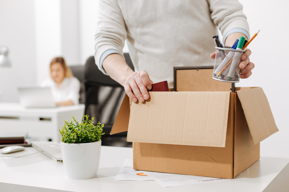 Employee clearing out desk after being pushed out of job